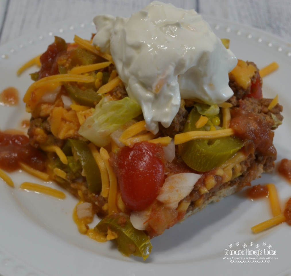 Taco Pizza Supreme is a mexican style pizza loaded with ground beef,sesoings,refried beans and cheese mixture.Taco toppings, sour cream and salsa round it off.