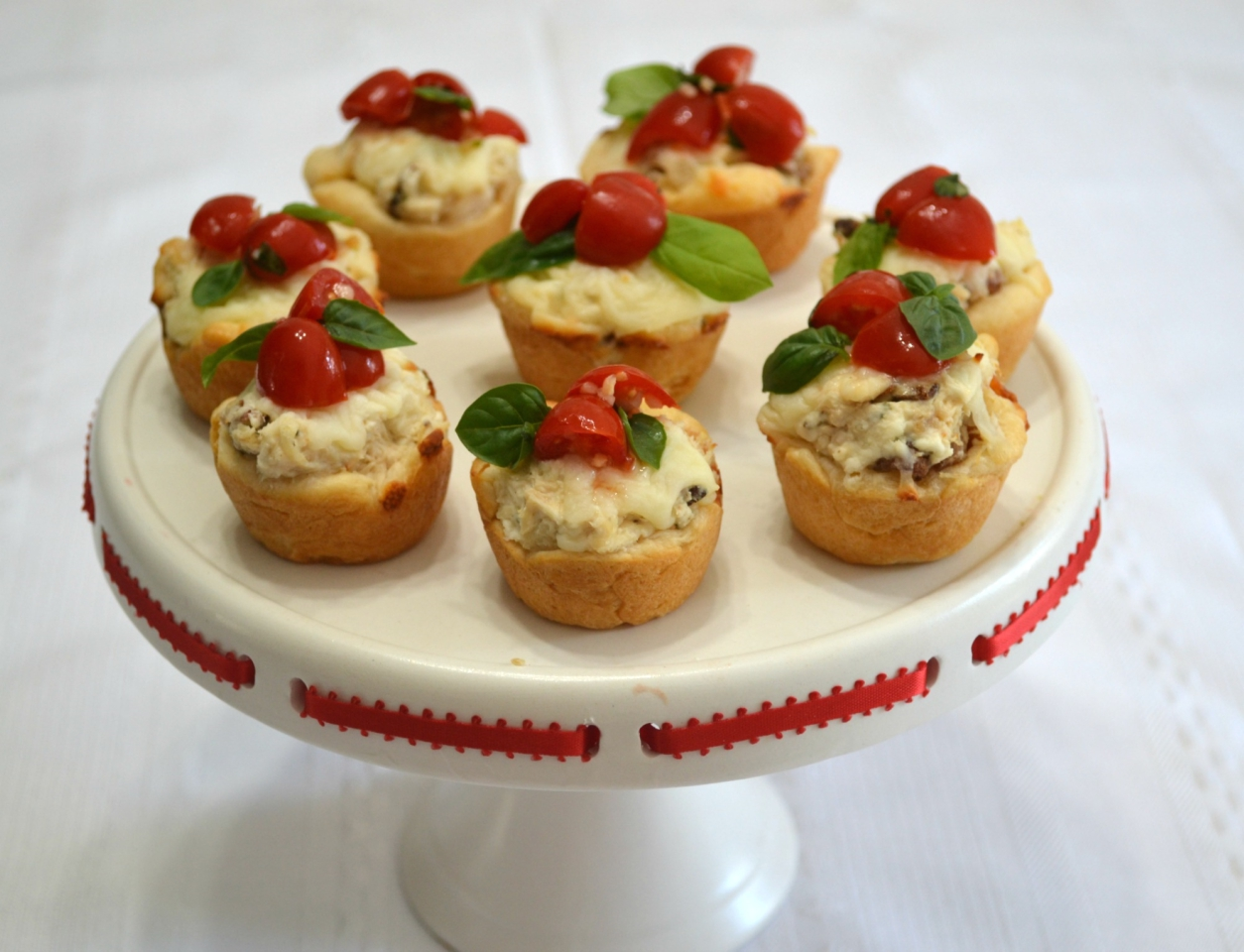 Chicken-Bacon-Caprese Bites are perfect to add to your tailgate menu. Chicken, cheese and a caprese topping baked in a crescent dough cup