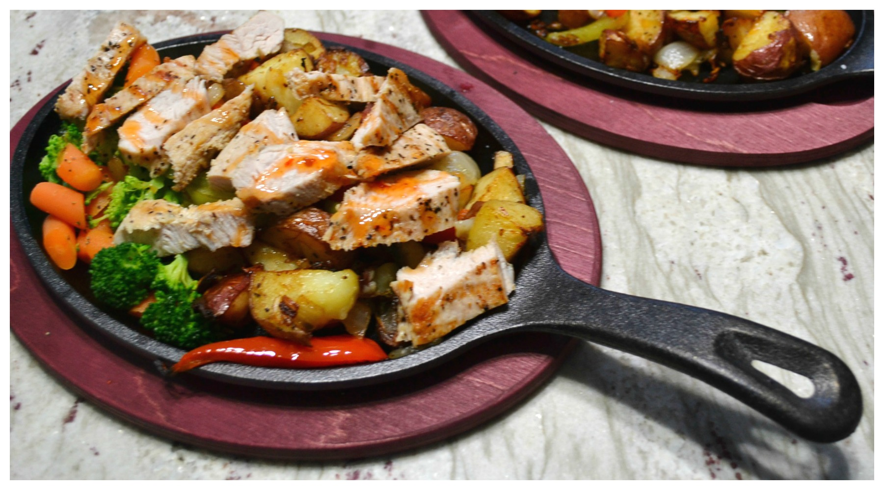 A sizzlin skillet filled with colorful veggies, sliced turkey cutlets and drizzled with sweet chili sauce.