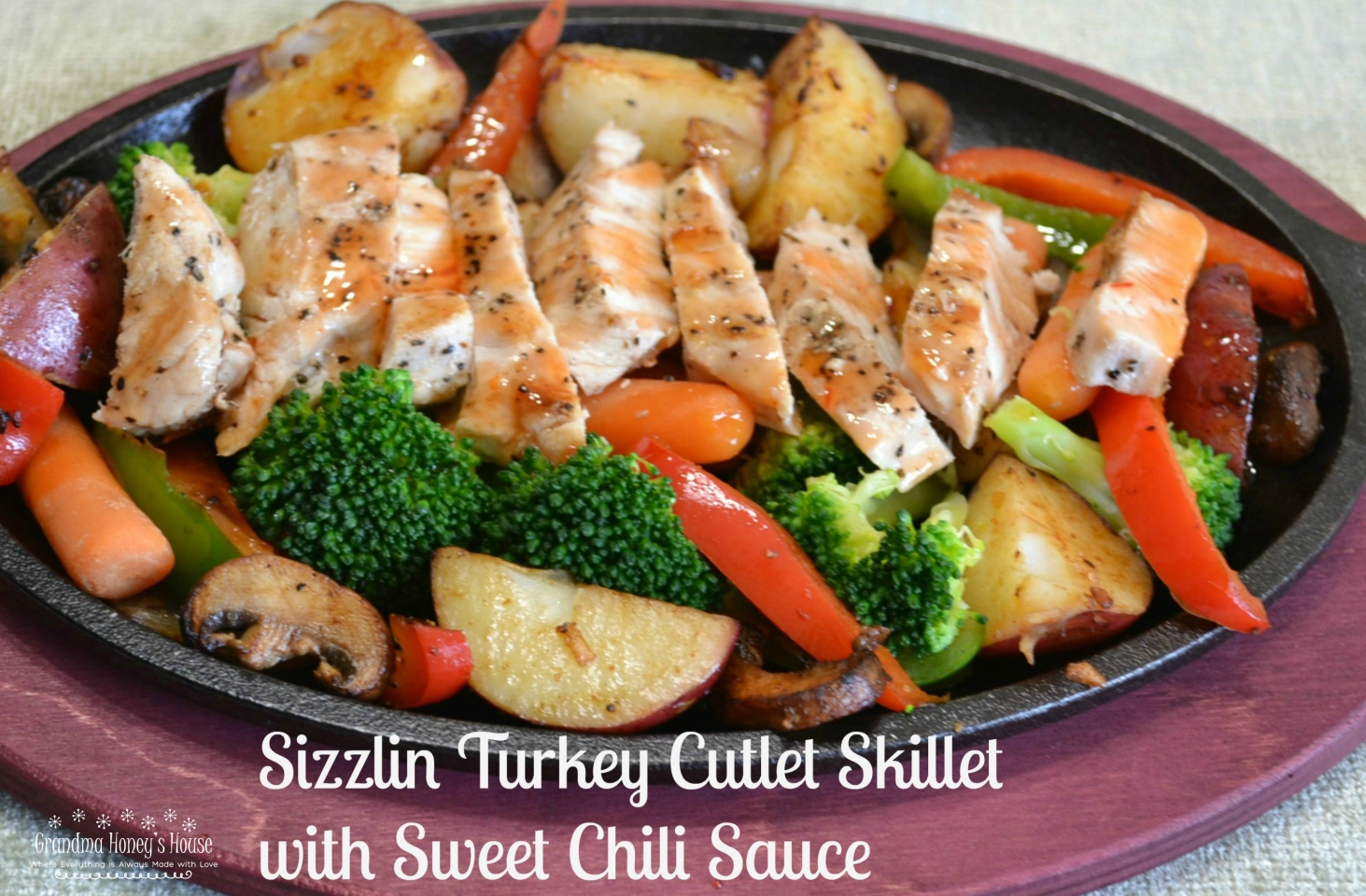 A healthy, colorful skillet dinner of fresh veggies, grilled turkey cutlets served on a cast iron skillet and drizzled with sweet chilli sauce.
