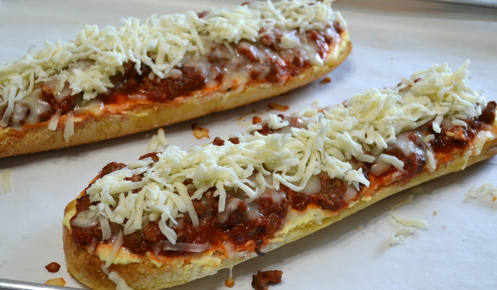 Loaves of garlic bread topped with a ricotta cheese layer, a meat sauce, and lots of melted mozzarella cheese. Perfect for dinner or cut into smaller pieces as an appetizer.