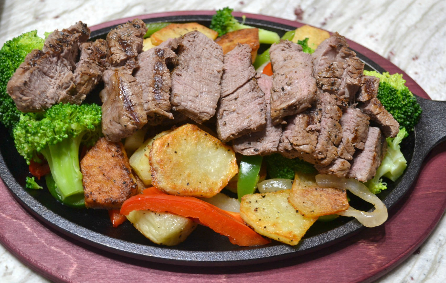 Steak and potato dinner with a delicious twist. Served with fresh veggies on a cast iron skillet