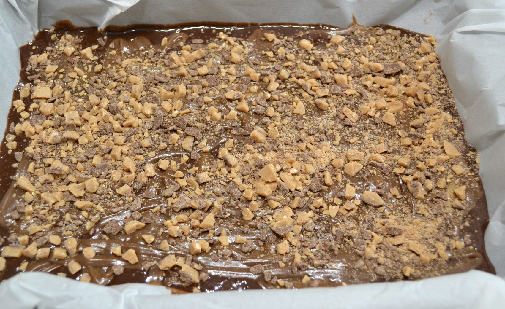 A decadent brownie dessert made with a can of chocolate flavored sweetened condensed milk, peanut butter, and toffee bits