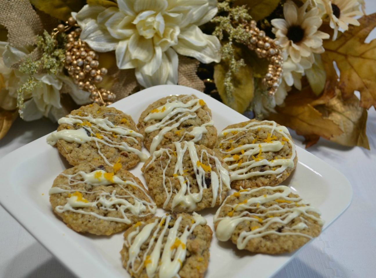 A flavorful oatmeal cookie packed with flavors from cranberry, pecans, and orange zest topped with a melted white chocolate drizzle.