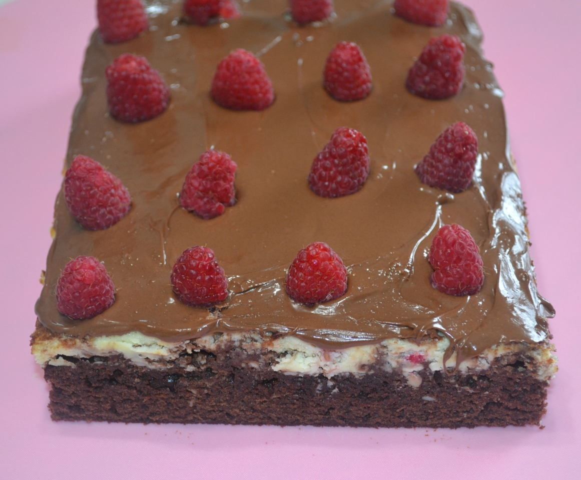 A rich, elegant brownies filled with chocolate chips, a cream cheese and raspberry filling, topped with melted chocolate.