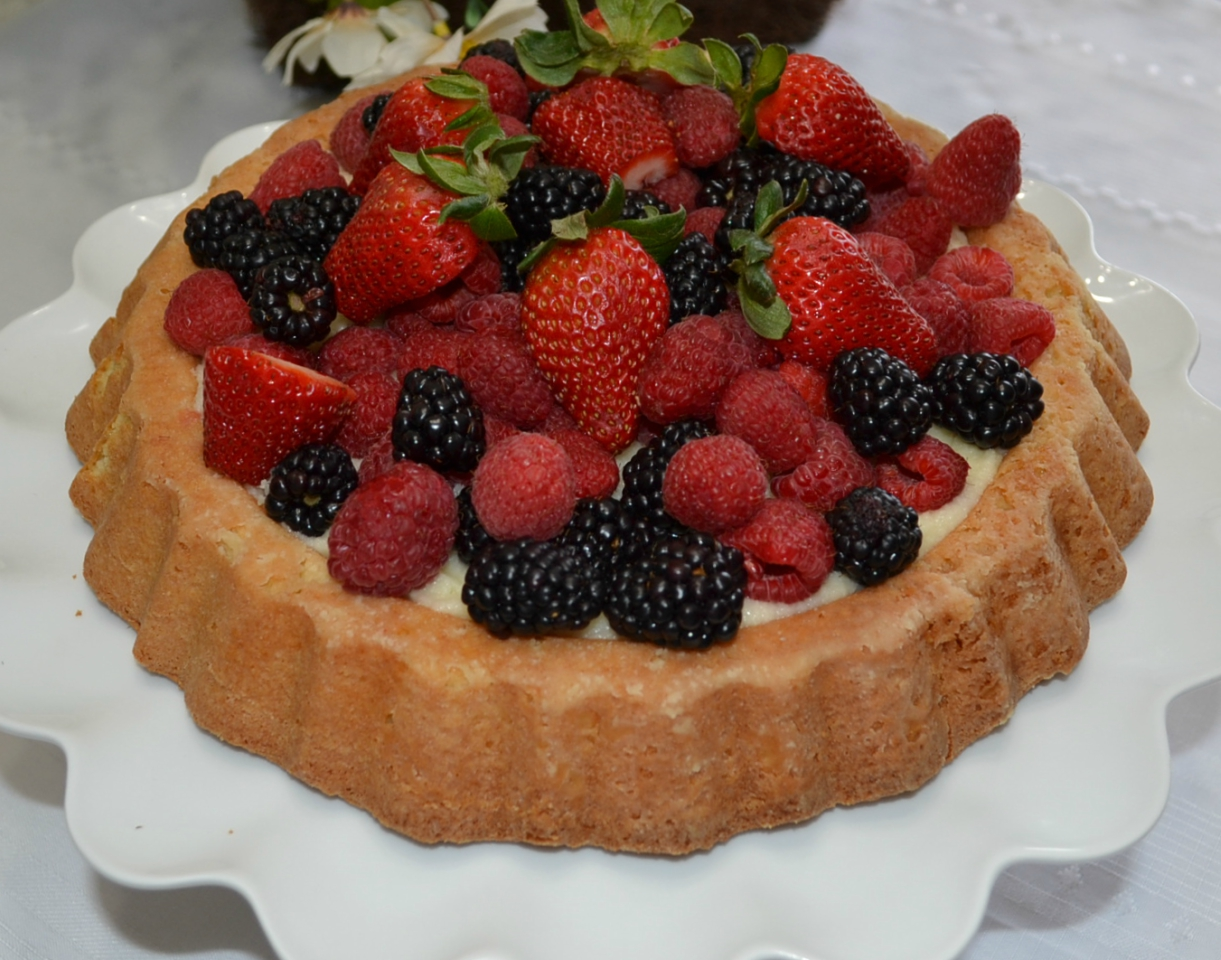 Raspberry Almond Tiara Cake is baked in a tiara pan, has almond paste in the cake, filled with a mascarpone layer and topped with fresh berries. Drizzle fresh raspberry sauce.