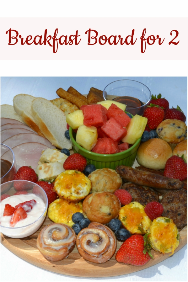 This Brunch Board for 2 is a delicious and fun way to enjoy a start to your day. A round, wooden cutting board is filled with a variety of breakfast foods, fresh fruits, dips, and sweet treats.