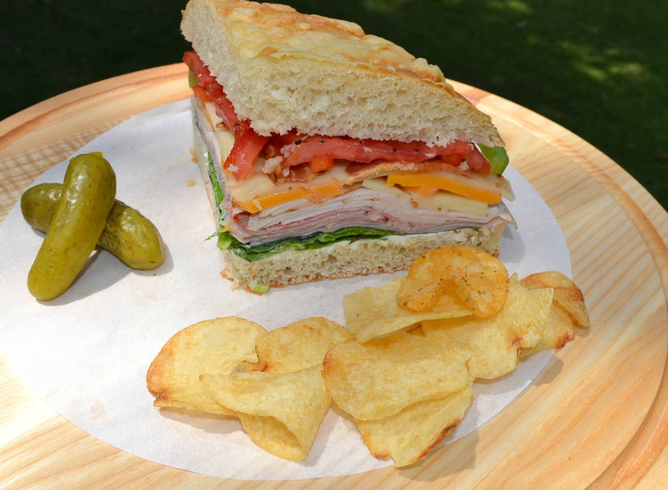 Picnic Foccacia Sandwich is loaded with meats, cheeses,and veggies. Made on a foccia loaf, drizzled with italian dressing and cut into beautiful wedges