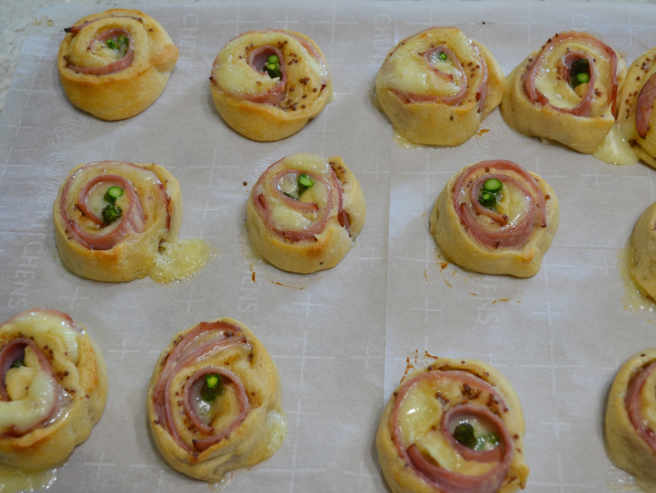 Ham-Brie-Asparagus Pinwheels are an easy appetizer with these ingredients baked in a crescent dough. They have a spread of honey mustard and warm, melted cheese.