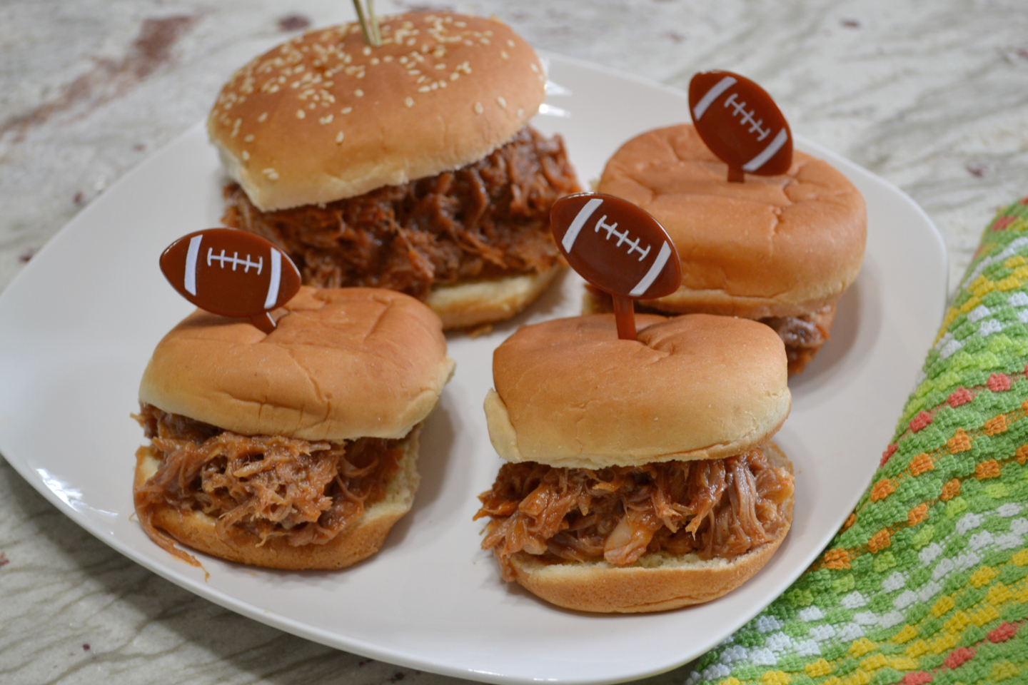 These Pulled Pork Sliders are perfect for any get together. Pork butt rubbed with a homemade rub,cooked in a crockpot, and covered with a homemade BBQ sauce.