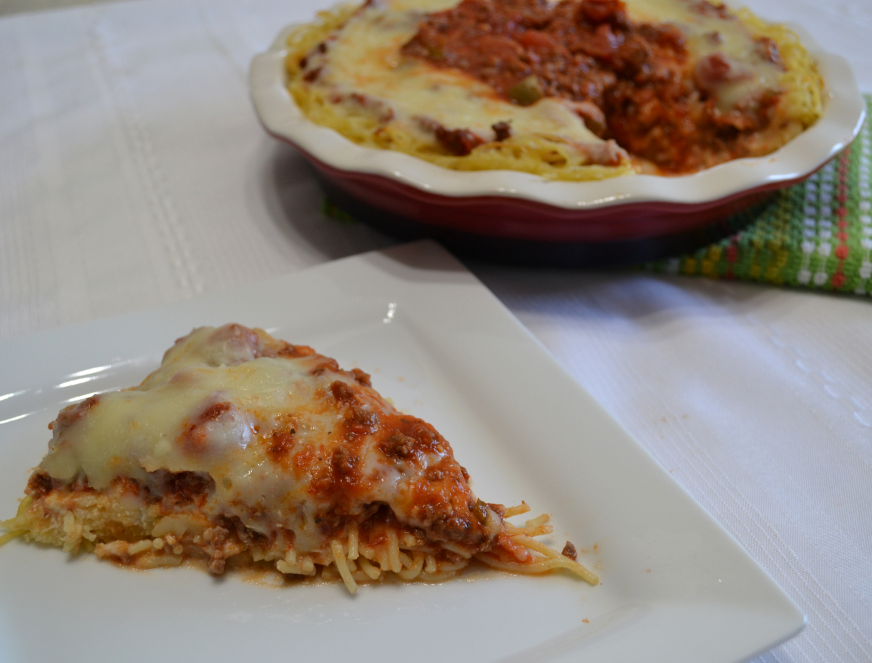 Cheesy Spaghetti Pie is baked in a deep dish pie plate with a crust of spaghetti,a layer of ricotta,then topped with homemade pasta sauce and mozzarella cheese.