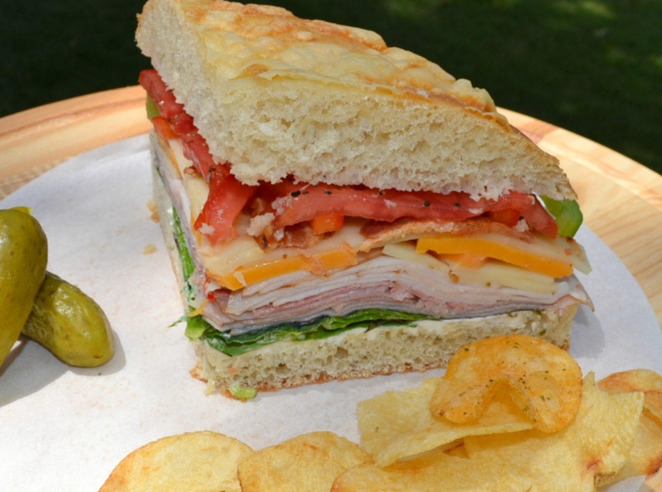 Picnic Foccacia Sandwich is loaded with meats, cheeses,and veggies. Made on a foccia loaf, drizzled with italian dressing and cut into beautiful wedges.