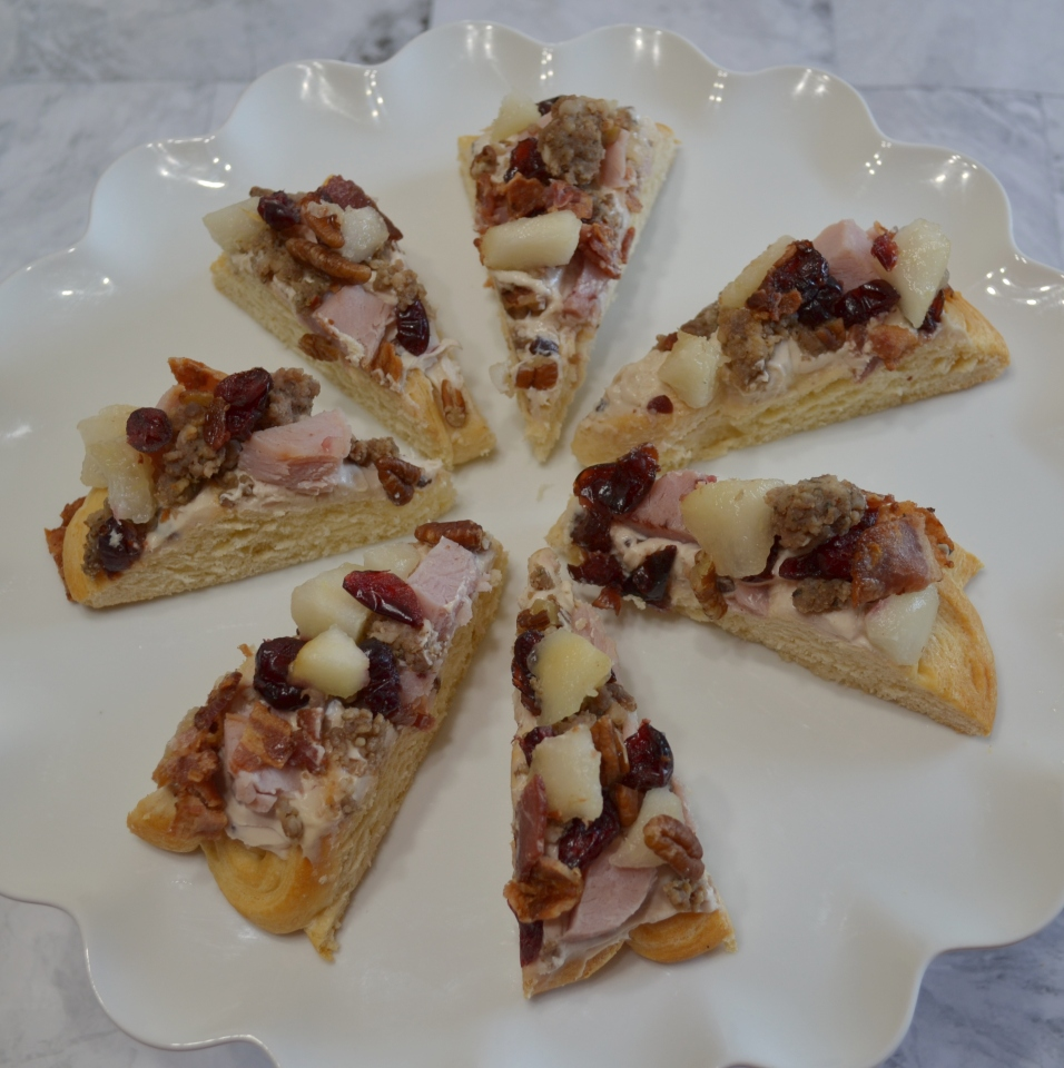 Holiday Pear Appetizer Wreath starts with a crescent crust,honey pecan cream cheese spread and topped with pears,ham,sausage,nuts,bacon,cranberries,and a drizzle of honey