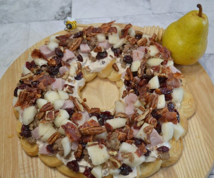 Holiday Pear Appetizer Wreath starts with a crescent crust,honey pecan cream cheese spread and topped with pears,ham,sausage,nuts,bacon,cranberries,and a drizzle of honey.