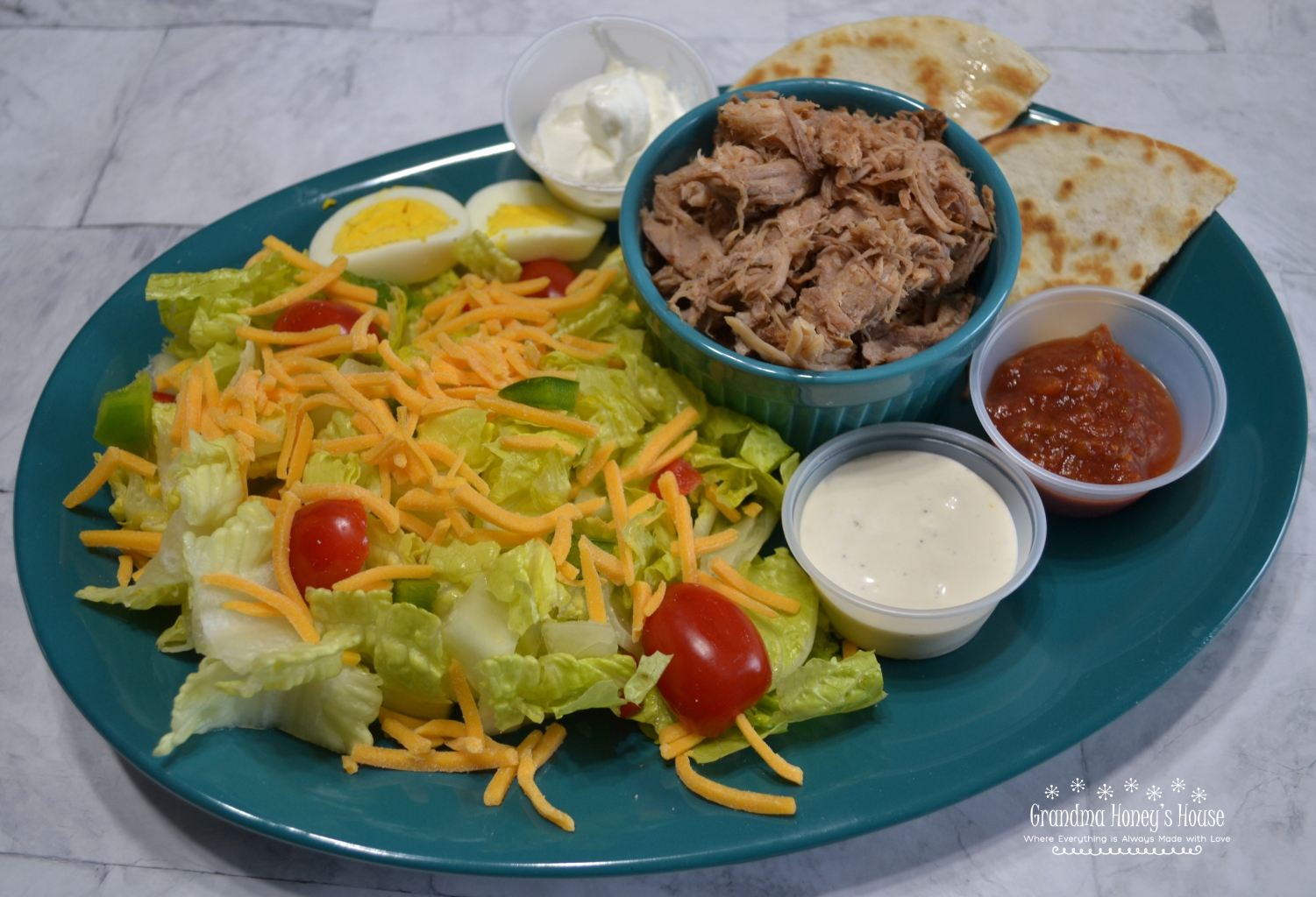BBQ Pulled Pork Salad is a slow cooked,tender pork butt with sauce served on a bed of lettuce,veggies,cheese and topped with ranch dressing.