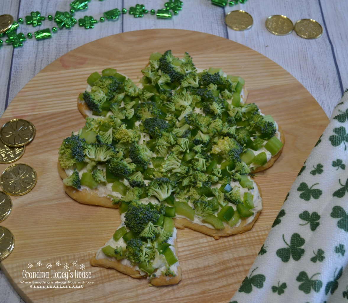 Shamrock Veggie Pizza is an easy appetizer made on a crescent dough crust, cream cheese and ranch filling, topped with green veggies for St Patrick's Day.