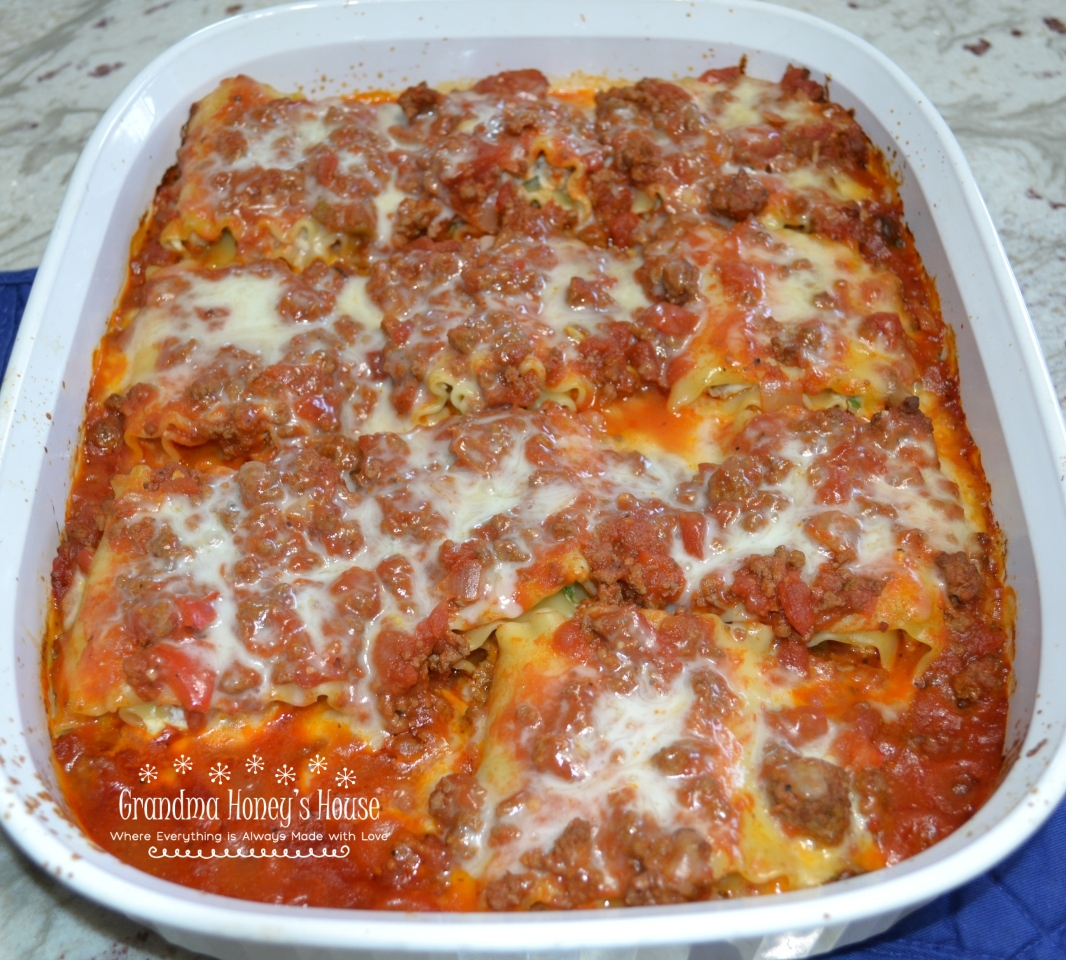 Sausage-Spinach Lasagna Roll-ups are a mixture of cheeses, egg, baby spinach, and sausage spread on lasagna noodles. They are rolled up,covered with pasta sauce and topped with more cheese and baked.