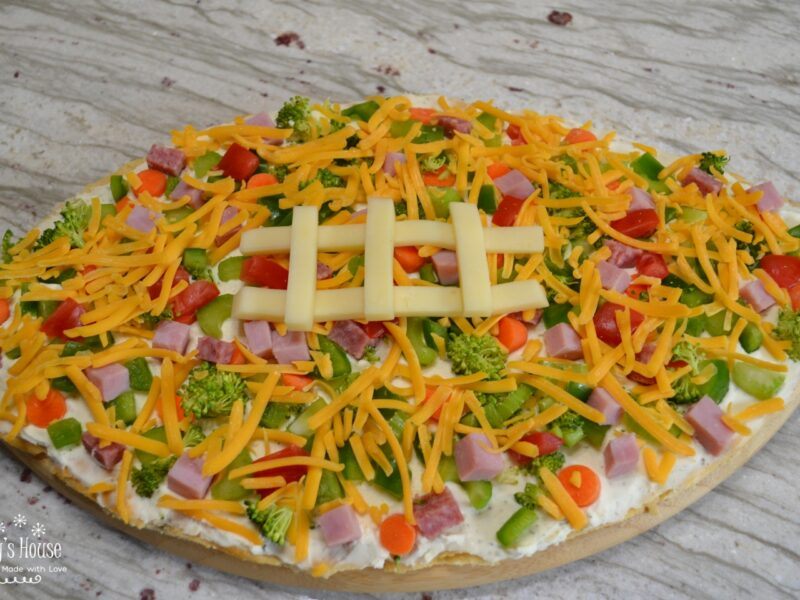 Loaded football veggie pizza is a crescent crust in a football shape, covered with cream cheese filling, veggies, meat and cheese. The perfect appetizer.